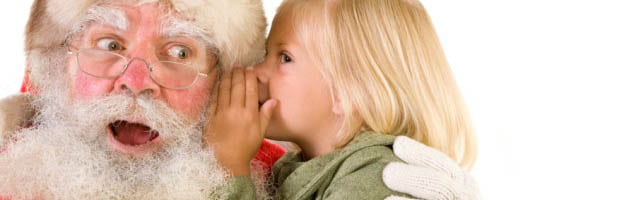 Little girl whispering in Santa's ear
